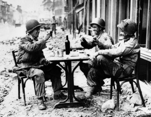 American GIs take a break and salute another day alive in La Haye du Puits, France, in July 1944.  AP Photo
