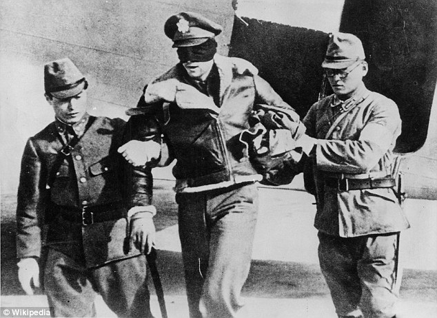 Colonel Robert Hite, of the Doolittle Raiders, is escorted by two Japanese soldiers after being captured in Japanese-occupied China in April 1942.